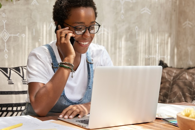 Stylish african american woman calls on smart phone looks in laptop computer, updates software