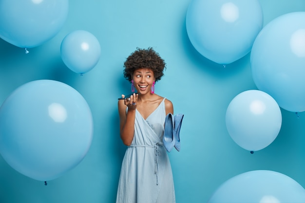 Stylish african american woman holds mobile phone near mouth, makes voice call, poses in stylish dress with high heel shoes, dresses for holiday event, stands indoor near inflated helium balloons.
