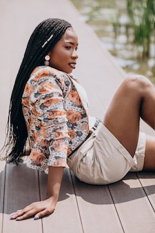 Стильная афро-американских женщина, сидя у озера в парке
