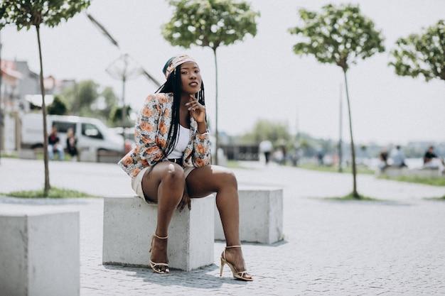 Donna afroamericana alla moda che si siede su una roccia nel parco