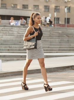 Stylish african american woman walking on crosswalk or pedestrian crossing.