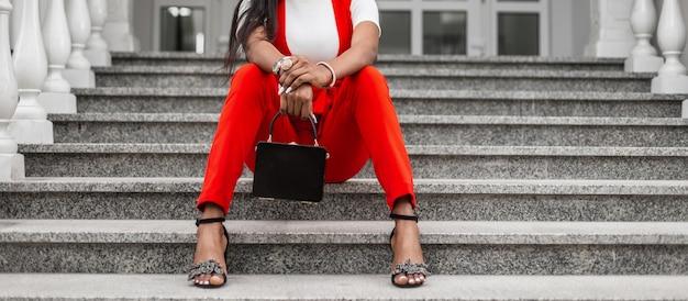 Стильная африканская черная женщина в модном красном костюме с сумкой и туфлями сидит на ступеньках в городе