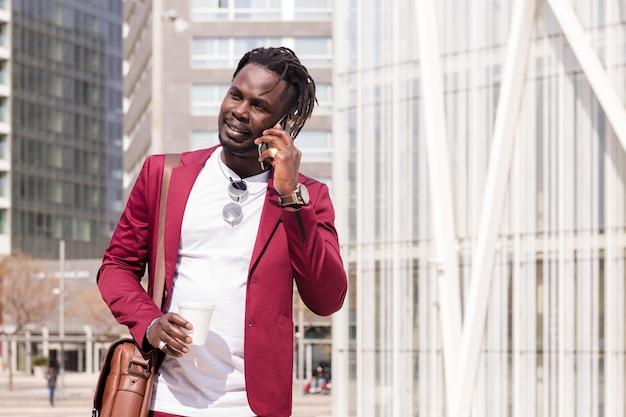 세련된 아프리카 사업가가 손에 커피를 들고 전화 통화를 하고 기술과 통신의 개념, 문자를 위한 복사 공간