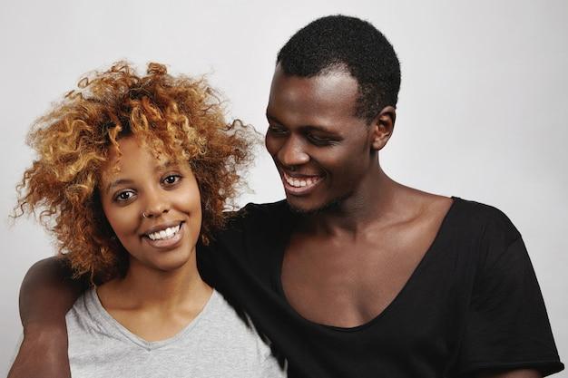 세련 된 아프리카 커플 포즈 : 아프로 헤어 스타일과 코걸이와 그의 아름다운 여자 친구를 껴안고, 다정한 미소로 그녀를보고 검은 티셔츠에 행복 잘 생긴 남자.