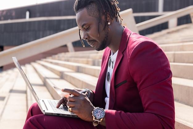 야외에 앉아 있는 세련된 아프리카 남성은 온라인 구매를 위해 신용카드로 결제한다