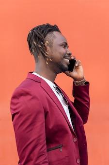 웃으면서 전화 통화를 하는 세련된 아프리카 남자