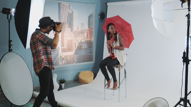 Stylish african model posing with red umbrella on bar high chair for fashion magazine photo shoot