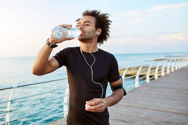 スタイリッシュなアフリカ系アメリカ人男性ランナーは、白いイヤホンを身に着けて、有酸素運動の後、ペットボトルから水を飲みます。屋外トレーニング中に水分補給する黒いスポーツウェアのスポーツマン。