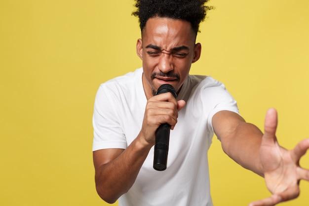 スタイリッシュなアフロアメリカの男は、イエローゴールドの背景に隔離されたマイクに歌う