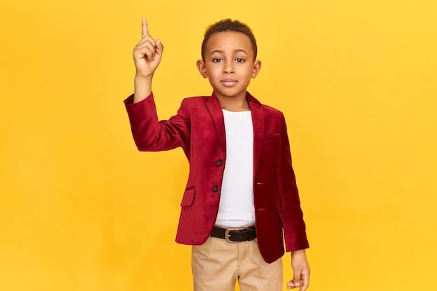 관심을 끌기의 표시로 앞 손가락을 올리는 우아한 옷을 입고 세련된 아프리카 계 미국인 남학생