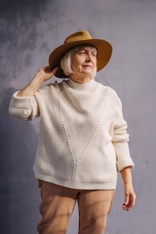 帽子に触れるスタイリッシュな老婆。ニットのセーターと流行の帽子の真面目な年配の女性