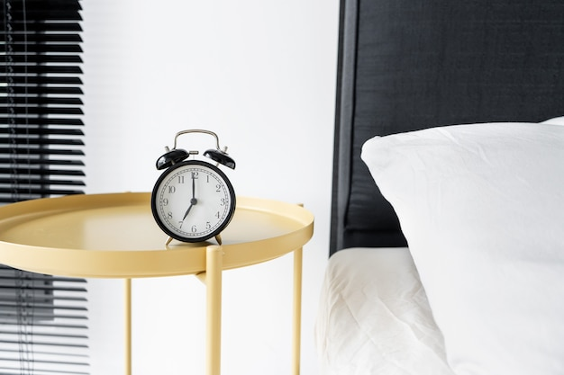 Stylish alarm clock with a bell. the hands show 7 hours. wake up time.