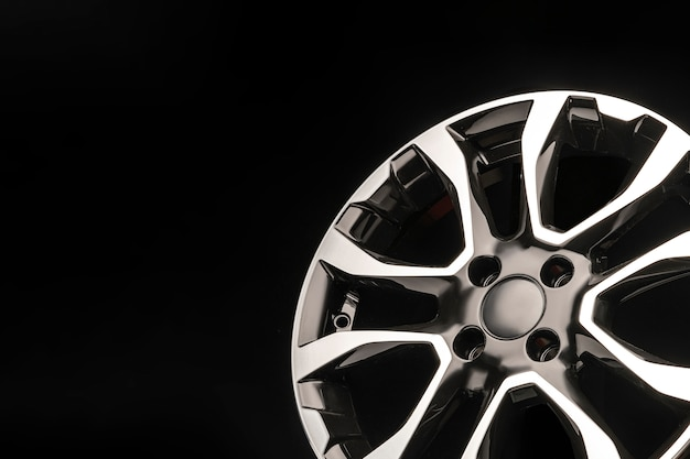 Stylish alloy wheels, black with silver and polished on a dark space. copyspace