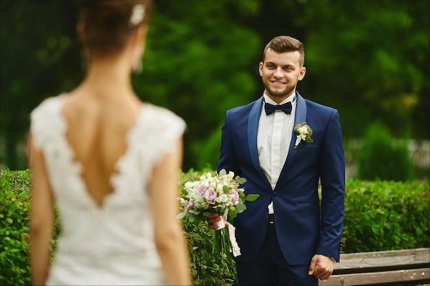 Стильный и бородатый молодой брутальный мужчина в элегантном костюме держит букет