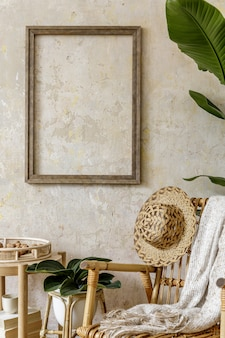 Стильная и бежевая композиция домашнего интерьера с креслом из ротанга, пустой рамой, журнальным столиком, книгой, подносом, декором, растениями и личными аксессуарами в летней концепции.