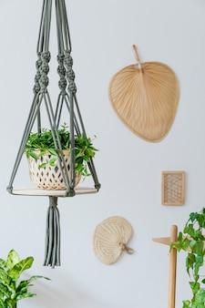 나무 책상, 의자, 램프 및 흰색 선반이있는 열린 공간의 세련되고 보헤미안 홈 인테리어. 디자인과 우아한 개인 액세서리. 식물학과 최소한의. 가정 장식. 벽에 추상 회화