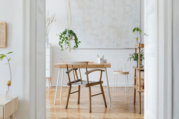 나무 책상 의자 램프와 흰색 선반이있는 작업 공간의 세련되고 boho 홈 인테리어 디자인 및 우아한 개인 액세서리 식물학 및 미니멀리즘 홈 데코 벽에 추상 그림