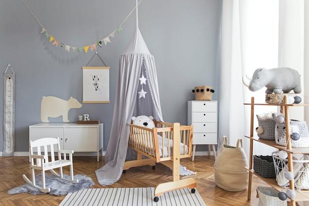ポスター、白いデザインの家具、自然のおもちゃ、木製のゆりかご、本立て、アクセサリー、テディベアと灰色の天蓋をぶら下げて新生児の部屋のスタイリッシュで明るいスカンジナビアの装飾
