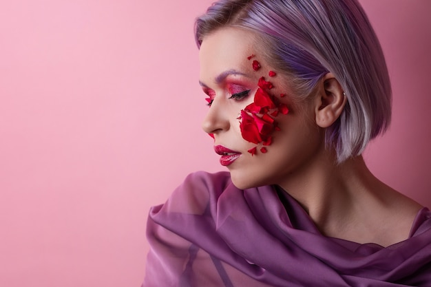 Стильная и яркая молодая женщина с цветным макияжем и лепестками цветов на лице
