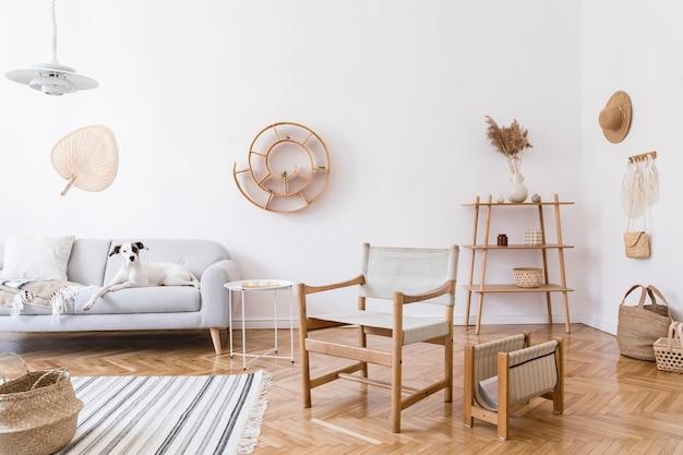 우아한 등나무 액세서리, 디자인 안락 의자, 회색 소파, 가구, 식물 및 나무 선반이있는 거실의 세련되고 아늑한 인테리어. 중립적 인 가정 장식.