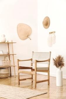 Стильный и уютный интерьер гостиной с аксессуарами из ротанга, дизайнерским креслом, цветами в вазе и деревянной полкой. корейский стиль домашнего декора.