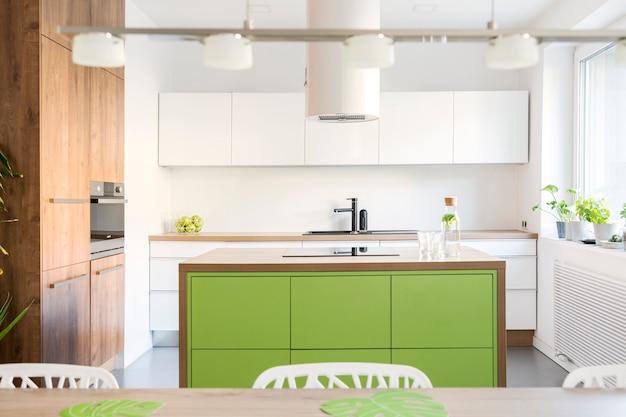 Стильный и креативный дизайн интерьера кухни с рабочим местом, обеденным столом, стульями и кухонными принадлежностями. современный стиль. светлое и просторное пространство