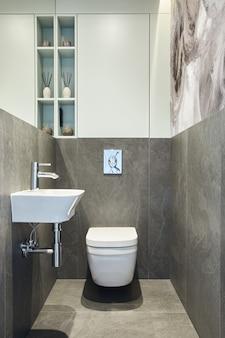대리석 벽, 식물 및 아름다운 욕실 액세서리로 세련되고 창의적인 최소한의 작은 욕실 인테리어 디자인. 최소한의 집 개념입니다.