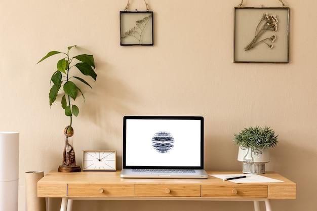 Стильный и креативный деревянный стол с экраном ноутбука, офисными принадлежностями из авокадо, растением и золотыми часами.