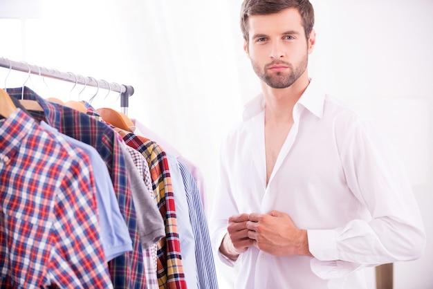 スタイリッシュでエレガンス。白いシャツを着て、カメラを見てハンサムな若い男