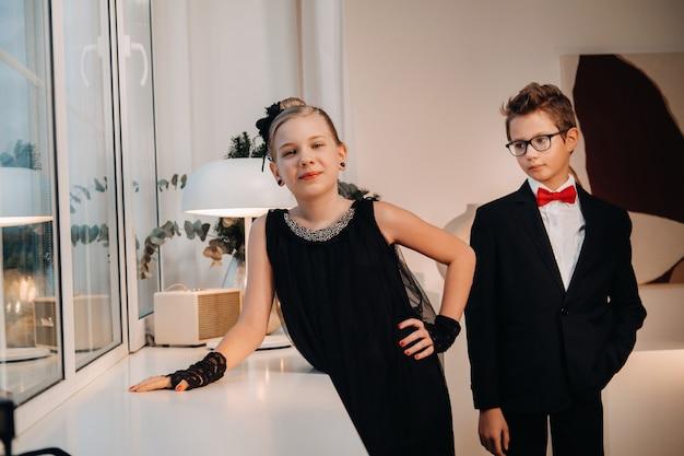 세련되고 우아한 소년과 소녀는 집 내부의 창문에 서 있습니다.