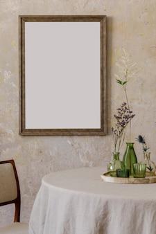 スタイリッシュでエレガントなダイニングルームのインテリア。ダイナーテーブル、デザインチェア、花瓶の花の花束、エレガントな籐の装飾が施されています。ポスターフレームをモックアップします。レンプレート。