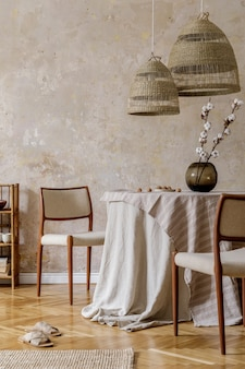 Стильный и элегантный интерьер столовой с обеденным столом, дизайнерскими стульями, подвесными светильниками из ротанга, красивыми цветами в вазах, мебелью, украшениями и элегантными личными аксессуарами в уютном домашнем декоре.