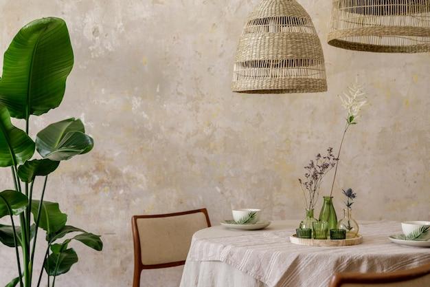 식당 테이블, 디자인 의자, 등나무 펜던트 램프, 꽃병의 아름다운 꽃, 가구, 장식 및 아늑한 가정 장식의 우아한 개인 액세서리가있는 세련되고 우아한 식당 인테리어.