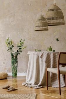 식당 테이블, 디자인 의자, 등나무 펜던트 램프, 꽃병에 든 아름다운 꽃, 가구, 장식 및 아늑한 가정 장식의 우아한 개인 액세서리가 있는 세련되고 우아한 식당 인테리어입니다.