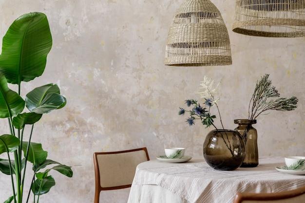 Стильный и элегантный интерьер столовой с обеденным столом, дизайнерскими стульями, подвесными светильниками из ротанга, чашками, букетом сухоцветов и элегантным декором. копировать пространство ..