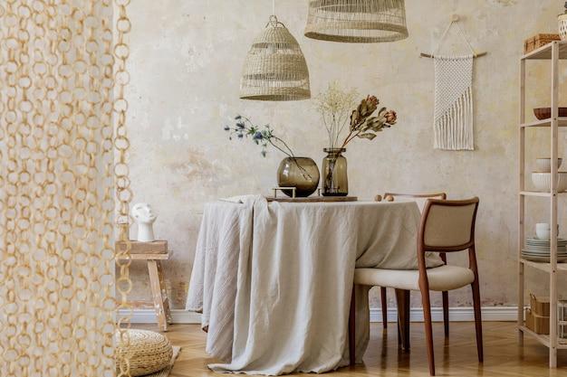 Стильный и элегантный интерьер столовой с обеденным столом, дизайнерскими стульями, подвесными светильниками из ротанга, засушенными цветами в вазах, мебелью, украшениями и элегантными личными аксессуарами в уютном домашнем декоре.