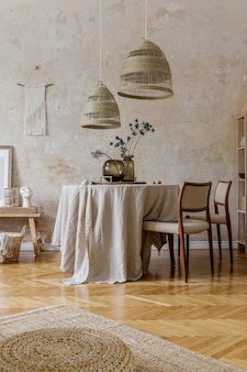 식당 테이블, 디자인 의자, 등나무 펜던트 램프, 꽃병에 말린 꽃, 가구, 장식 및 아늑한 가정 장식의 우아한 개인 액세서리를 갖춘 세련되고 우아한 식당 인테리어.