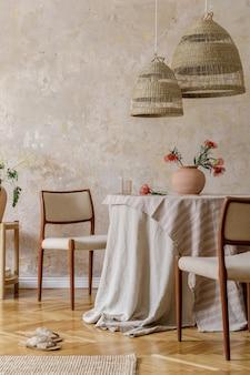 식당 테이블, 디자인 의자, 등나무 펜던트 램프, 꽃병에 말린 꽃, 가구, 장식 및 아늑한 가정 장식의 우아한 개인 액세서리가 있는 세련되고 우아한 식당 인테리어입니다.