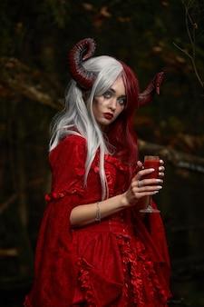 神秘的な森の中でポーズをとるマレフィセントをイメージしたスタイリッシュでファッショナブルなモデルの女の子-おとぎ話、コスプレ。ハロウィーン。