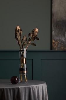 エレガントなアクセサリーを備えたデザイン テーブルのモダンな花瓶に、スタイリッシュで美しい花の構成。ミニマル。リビング ルームの花のコンセプト。緑の壁。インテリア・デザイン..