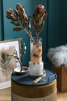 エレガントなアクセサリーと家具を備えた、ベルベットのプーフのモダンな花瓶に美しい花のスタイリッシュで花の構成。リビング ルームの花のコンセプト。緑の壁。インテリア・デザイン..