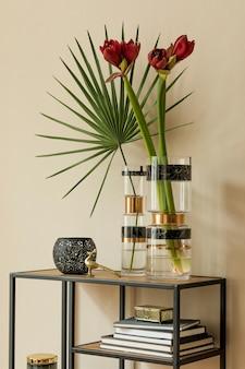 우아한 액세서리와 함께 디자인 선반에 현대 꽃병에 있는 아름 다운 꽃의 세련 되 고 꽃 구성. 베이지색 벽에 그림자가 있는 꽃 컨셉입니다. 인테리어 디자인. 주형.