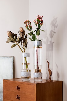 우아한 액세서리와 함께 복고풍 나무 화장실에 현대 꽃병에 아름 다운 꽃의 세련 되 고 꽃 구성. 베이지색 벽에 그림자가 있는 꽃 컨셉입니다. 인테리어 디자인. 주형.