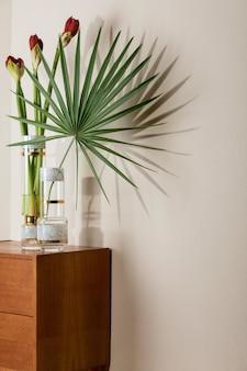 エレガントなアクセサリーとレトロな木製の便器のモダンな花瓶の美しい花のスタイリッシュで花の構成。ベージュの壁に影のある花のコンセプト。インテリア・デザイン。レンプレート。