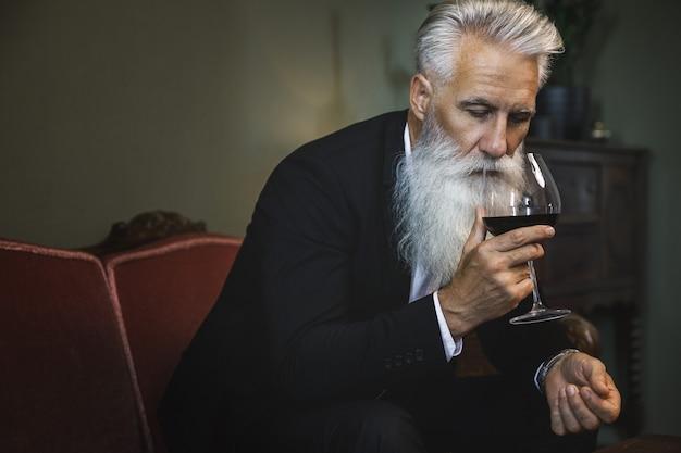 레드 와인을 마시는 세련 되 고 잘 생긴 수염 된 수석 남자