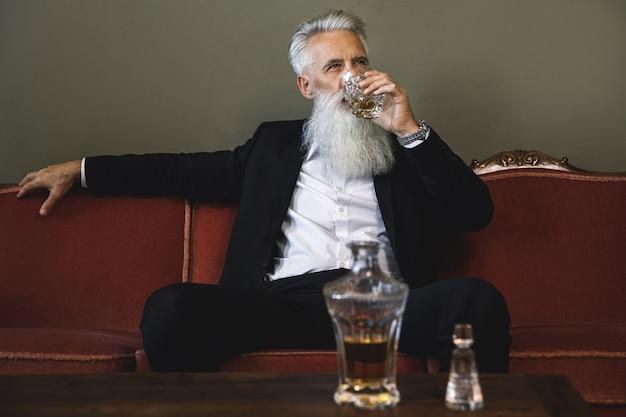 세련 되 고 잘 생긴 수염 된 수석 남자 위스키를 마시는