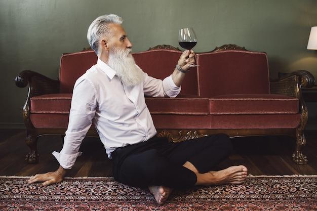 Стильный и красивый бородатый старший мужчина сидит на полу и пьет красное вино