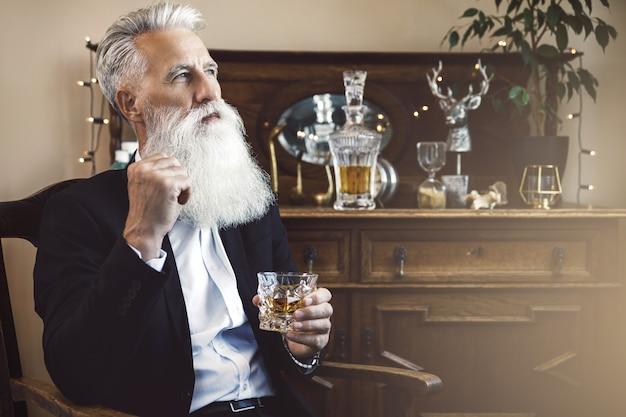 ウイスキーのグラスとスタイリッシュでハンサムなひげを生やした年配の男性