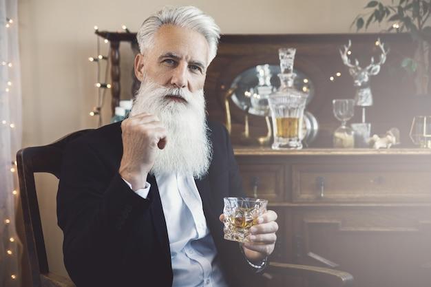 위스키 한잔과 함께 세련되고 잘 생긴 수염 난 수석 남자