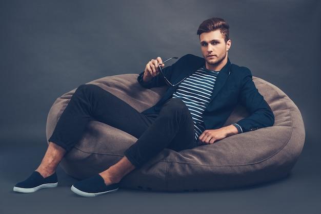 Стильно и красиво. уверенный молодой красивый мужчина держит солнцезащитные очки и смотрит в камеру, сидя на мешке с фасолью на сером фоне